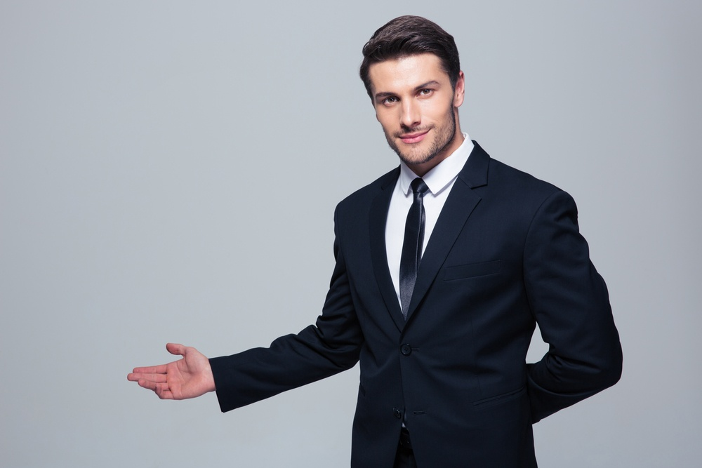 Businessman with arm out in a welcoming gesture over gray background